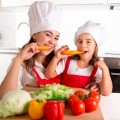 happy mother and little daughter in apron and cook hat eating carrots together having fun at home kitchen