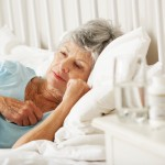 Medication On Bedside Table Of Sleepless Senior Woman
