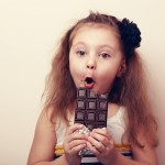 Surprised girl with open mouth holding chocolate and looking
