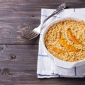 Crumble with pumpkin and cheese in white dish on the wooden table