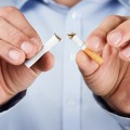 Quit smoking concept of man tearing cigarette in half