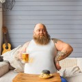Confident fat man resting with alcohol beverage